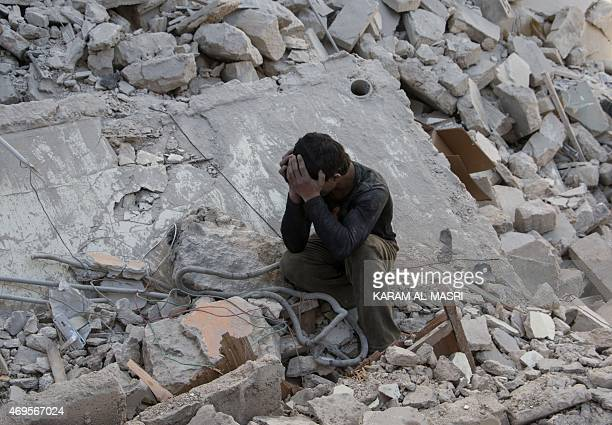 A Syrian boy mourns in the rubble of a building following a reported air strike by government forces on the rebel held area in the east of the...