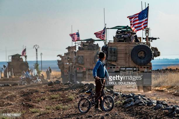 Syrian boy on his bicycle looks at a convoy of US armoured vehicles patrolling fields near the northeastern town of Qahtaniyah at the border with...