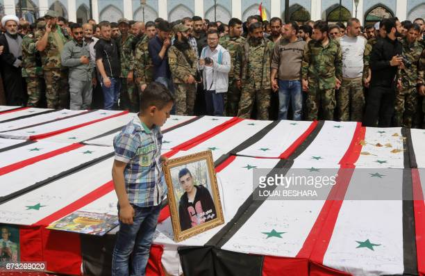 A Syrian boy places a picture on top of a coffin during a funeral ceremony in the Sayyida Zeinab mosque on the outskirts of Damascus on April 26 for...