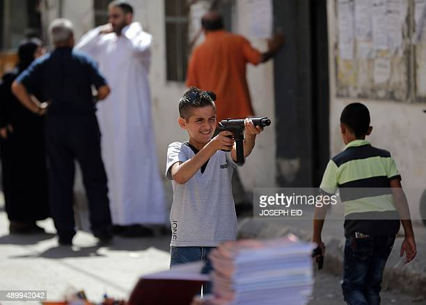 A Syrian boy plays with a toy gun in the Mediterranean port city of Latakia on September 24 on the first day of the Muslim holiday of Eid alAdha Eid...