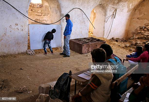 Syrian boy practices basic arithmetic operations with a teacher during class in a barn that has been converted into a makeshift school to teach...