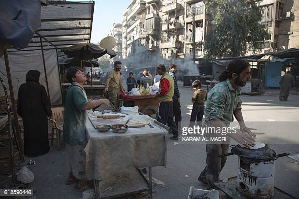 A Syrian boy prepares manakish in the rebelheld side of the northern embattled city of Aleppo on October 27 2016 Regime forces backed by ally Russia...
