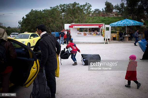 Syrian boy pulls a bag while other family members try to get a taxi outside a registration camp, which brings them to the port of Mytelene in order...