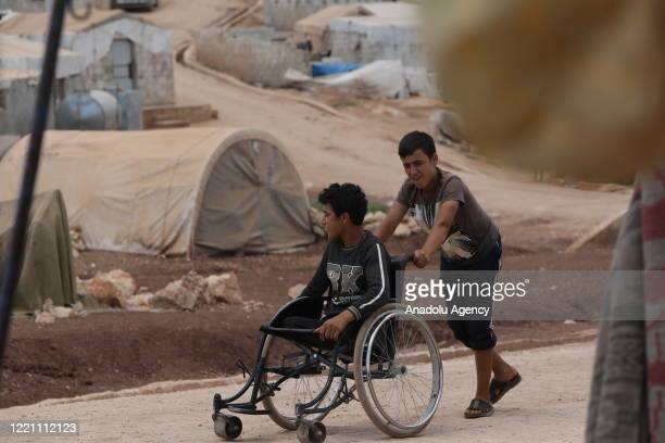 Syrian boy pushes his disabled friend's wheelchair at a refugee camp where thousands of displaced Syrians shelter due to Assad Regime forces and its...