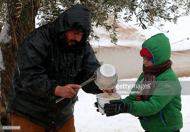Syrian boy receives food aid in a plastic bucket at a tent city as it snows in the Azaz town of Aleppo Syria on December 21 2016