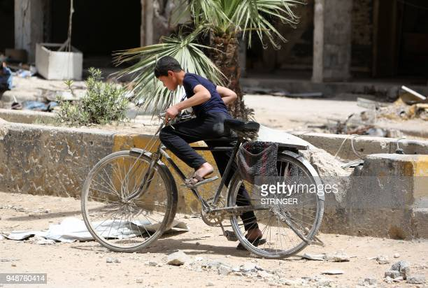A Syrian boy rides a bicycle in the former rebelheld Syrian town of Douma on the outskirts of Damascus on April 19 five days after the Syrian army...