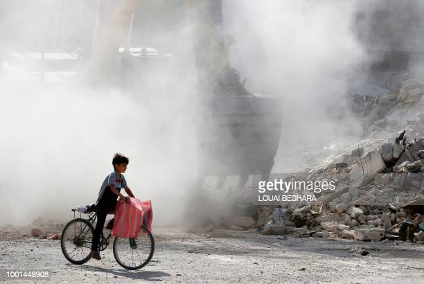 A Syrian boy rides his bicycle amid the rubble of destroyed buildings being removed by a bulldozer in Harasta on the outskirt of the Syrian capital...