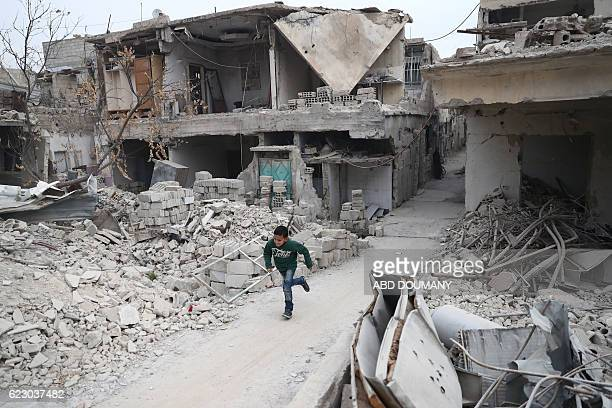 A Syrian boy runs between the rubble of destroyed buildings in the rebelheld town of Douma on the eastern outskirts of the capital Damascus on...
