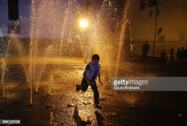 A Syrian boy runs next to a fountain outside the Umayyad Mosque in the Old City of the capital Damascus on June 14 2017 / AFP PHOTO / Louai Beshara