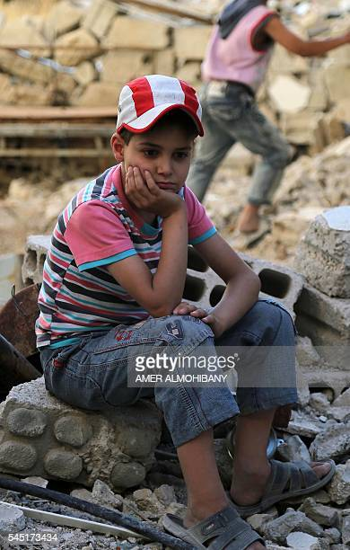A Syrian boy sits amidst destruction during an activity organised by a charity group in Jobar a rebelheld district on the eastern outskirts of the...