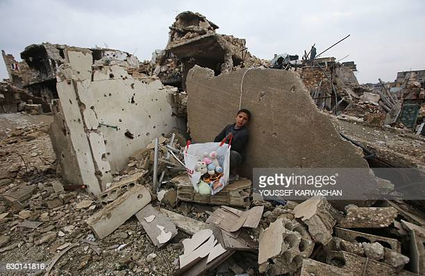 Syrian boy sits with belongings he collected from the rubble of his house in Aleppo's AlArkoub neighbourhood on December 17 after progovernment...