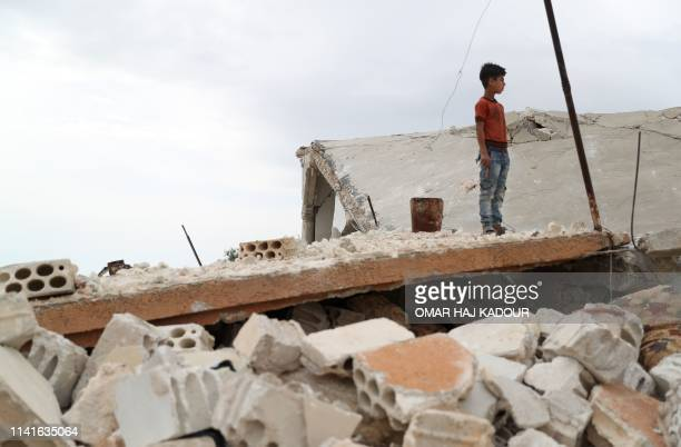 Syrian boy stands above the rubble of a building in the village of Rabaa Jour in the the jihadist-held Syrian province of Idlib on May 6, 2019...
