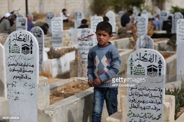 A Syrian boy stands amid graves during the funeral of victims of a reported government shelling in the rebelheld besieged town of Jisreen east of the...