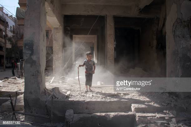 Syrian boy stands amidst the rubble of a building in the rebelheld town of Douma on the eastern outskirts of Damascus on October 6 2017 following...