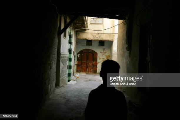 Syrian boy stands at the entrance to a street on May 21 2005 in the old streets of Damascus Syria Syrian President Bashar alAssad has vowed to...
