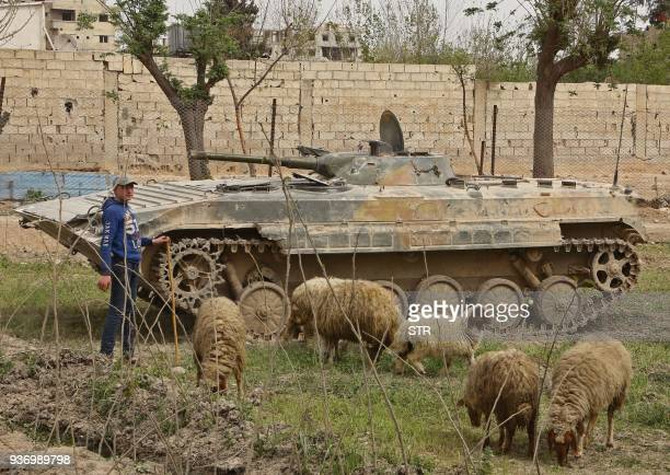 Syrian boy stands next to an armoured vehicle as sheep graze nearby in a regimecontrolled area on the outskirts of the Eastern Ghouta town of Ain...
