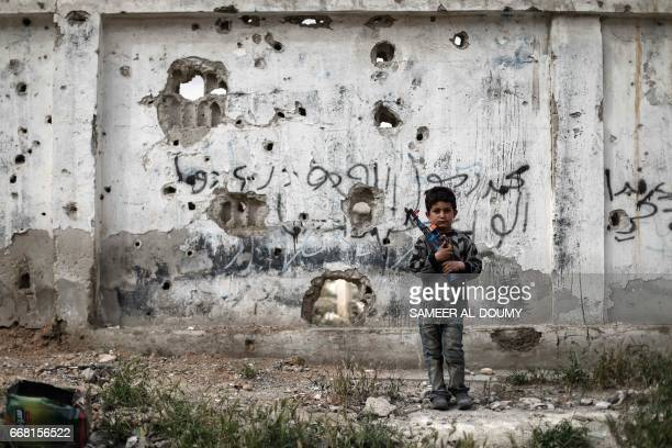 Syrian boy stands with a toygun in front of a bulletriddled wall in the rebelheld town of Douma on the eastern outskirts of the Syrian capital...