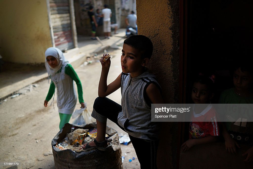 A Syrian boy stands with siblings outside of the home they are renting in a poor neighborhood with a high concentration of Syrian refugees on June 30, 2013 in Beirut, Lebanon. Currently the Lebanese government officially hosts 546,000 Syrians with an estimated additional 500,000 who have not registered with the United Nations. Lebanon, a country of only 4 million people, is now home to the largest number of Syrian refugees who have fled the conflict. The situation is beginning to put a huge social and political strains on Lebanon as there is currently no end in sight to the war in Syria.