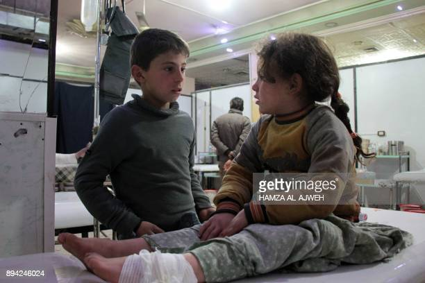 Syrian boy talks to an injured girl as she lies on an operating bed in an emergency room in the rebelheld town of Douma in Syria's eastern Ghouta...