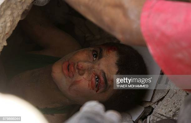 A Syrian boy trapped under the rubble of buildings destroyed following reported air strikes on the rebelheld neighbourhood of AlMashhad in the...