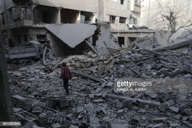 Syrian boy walk past destruction following government air strikes in the Eastern Ghouta rebelheld enclave of Douma on the eastern outskirts of the...