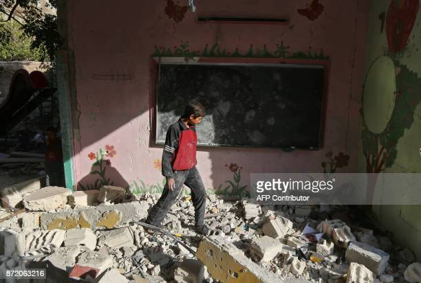 A Syrian boy walks amid the rubble inside his damaged school on November 9 2017 in the besieged rebelheld Eastern Ghouta town of Hamouria on the...
