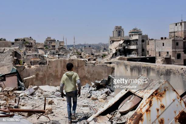 Syrian boy walks amid the rubble of destroyed buildings on July 22 in the northern city of Aleppo, which was recaptured by government forces in...