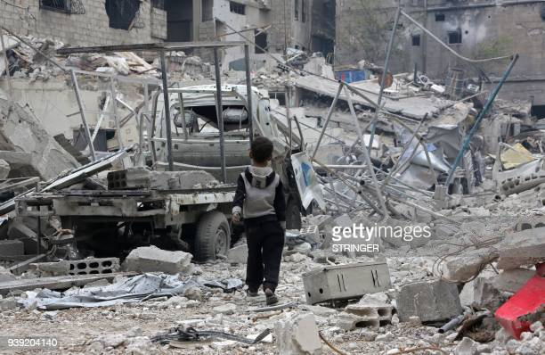 Syrian boy walks past debris, rubble, and a damaged vehicle in the town of Hazzeh in Eastern Ghouta, on the outskirts of the Syrian capital Damascus,...
