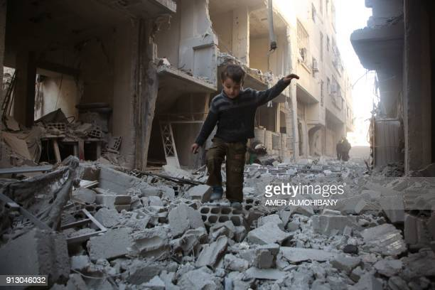Syrian boy walks through a street covered with rubble from a heavily damaged building following air strikes by regime forces in Arbin, in the...