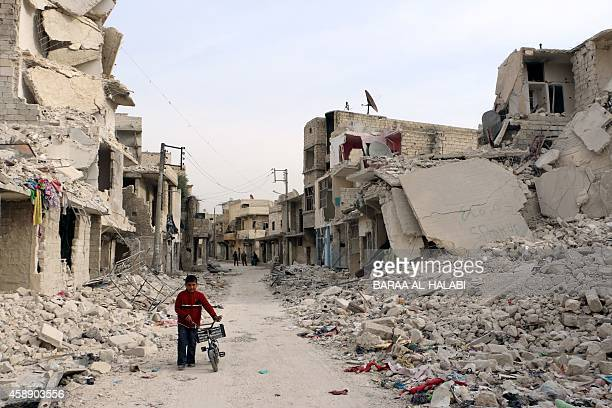 A Syrian boy walks with his bicycle in the devastated Sukari district in the northern city of Aleppo on November 13 after more than three years of...