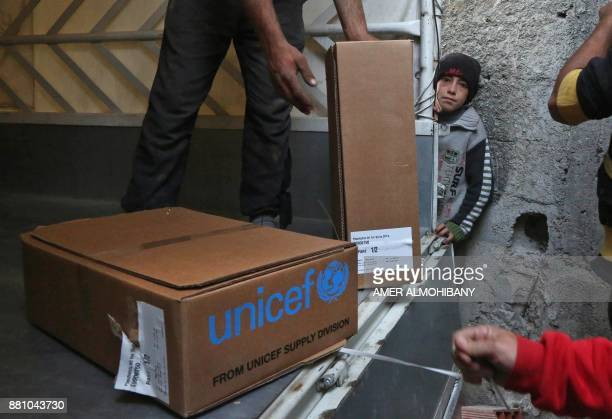 A Syrian boy watches as aid packages provided by the International Committee of the Red Cross in a joint operation with the UN are unloaded in the...