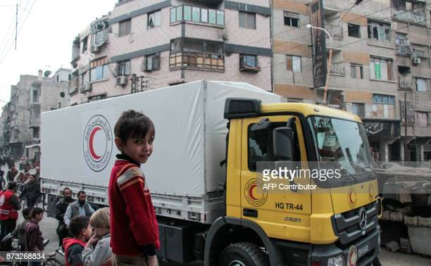 A Syrian boy watches as packages humanitarian relief provided by the International Committee of the Red Cross in a joint operation with the UN are...