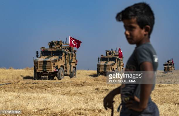 Syrian boy watches as Turkish military vehicles part of a US military convoy take part in joint patrol in the Syrian village of alHashisha on the...