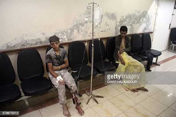 TOPSHOT Syrian boys await treatment at a makeshift hospital following strikes and shelling on the rebelheld northwestern city of Idlib late on July...
