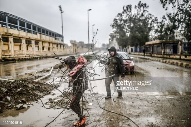Syrian boys carry scrap irons bars and rods from rubble outside Raqa stadium in the eastern Syrian city on February 14, 2019. - In 2014, jihadists of...