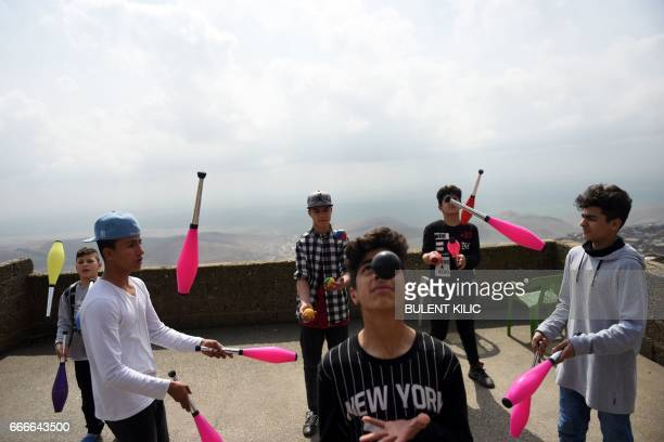 Syrian boys juggle on a roof top of a house on March 19 in Mardin There is laughter excitement and a sense of joyful chaos Some children are perched...