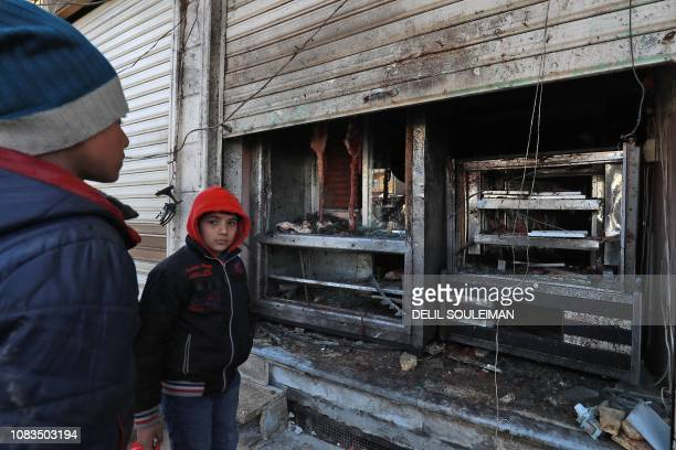 Syrian boys look at the destroyed grills outside a shuttereddown restaurant which was the site of a suicide attack targeting USled coalition forces...