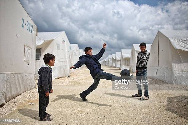 Syrian boys play football in Suruc refugee camp on March 25, 2015 in Suruc, Turkey. The camp is the largest of its kind in Turkey with a population...