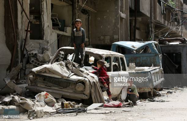 TOPSHOT Syrian boys play on a destroyed car in the former rebelheld Syrian town of Douma on the outskirts of Damascus on April 19 five days after the...