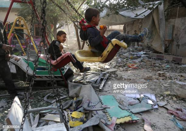 Syrian boys play on swings in the playground of their damaged school on November 9 2017 in the besieged rebelheld Eastern Ghouta town of Hamouria on...
