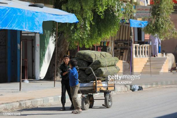 Syrian boys pull a cart in the rebel-controlled town of Tal Abyad in Syria's northern Raqa province, on October 11, 2020. - UN High Commissioner for...