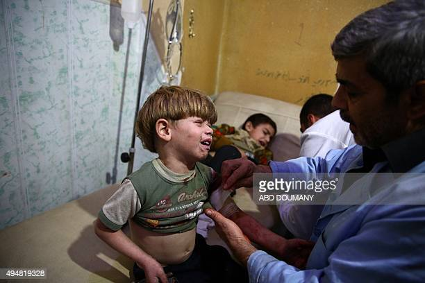 Syrian boys receive treatment at a makeshift hospital following reported air strikes by government forces in the rebelheld area of Douma east of the...
