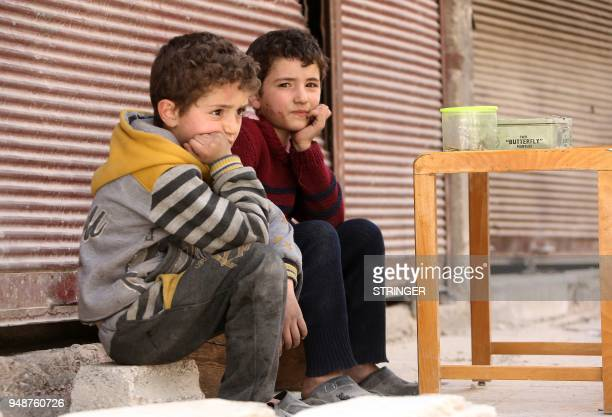 Syrian boys sit in the street in the former rebelheld Syrian town of Douma on the outskirts of Damascus on April 19 five days after the Syrian army...