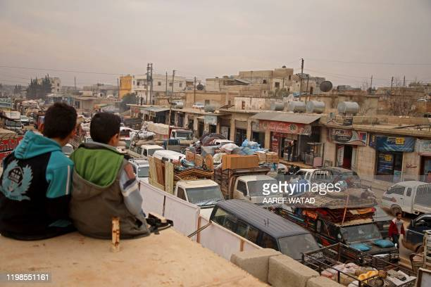 Syrian boys sitting on a ledge watch traffic in the town of Hazano in the northern countryside of Idlib, on February 4 as people flee northwards in...