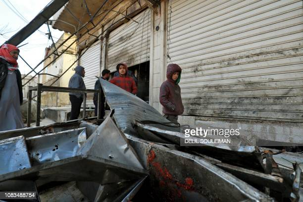 Syrian boys stand outside a shuttereddown restaurant which was the site of a suicide attack targeting USled coalition forces in the flashpoint...