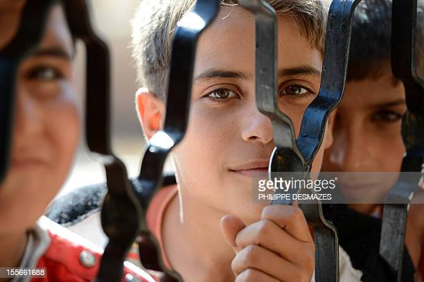 Syrian boys wait for food behind an iron door at a school housing around 140 refugees in the village of Atme in the Idlib province near the border...