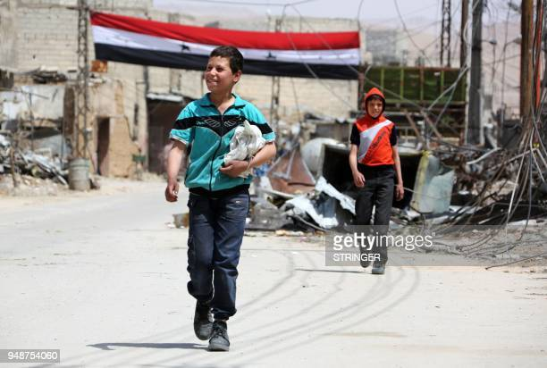 Syrian boys walk along a street in the former rebelheld Syrian town of Douma on the outskirts of Damascus on April 19 five days after the Syrian army...