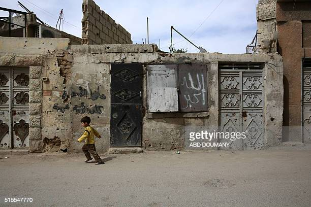A Syrian boys walks in the alQaboun rebel held northeastern suburb of the capital Damascus on March 13 2016 One in three Syrian children have known...