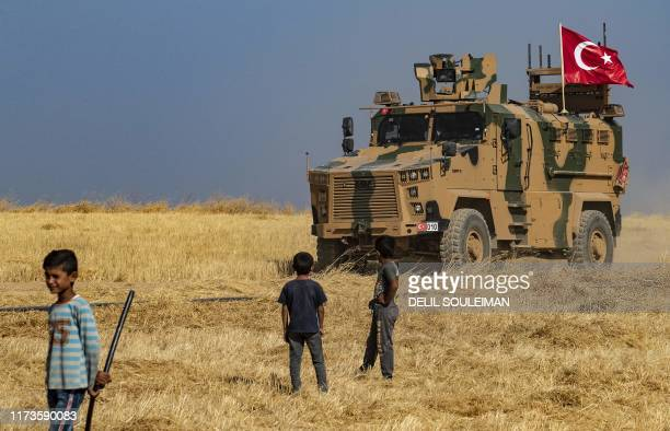Syrian boys watch as a Turkish military vehicle patrols along with the US military the Syrian village of al-Hashisha on the outskirts of Tal Abyad...