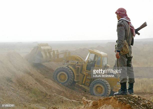 Syrian bulldozer is seen guarded by a security man at the Syrian AlBukamal border point 550 Kms northeast of Damascus during the construction of a...